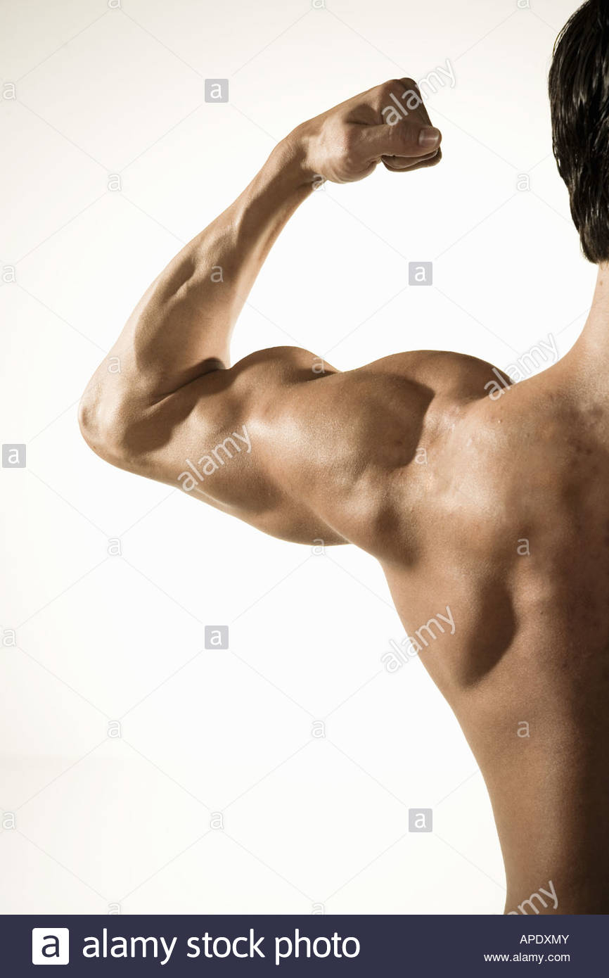 Bare-chested man flexing biceps muscles - Stock Image