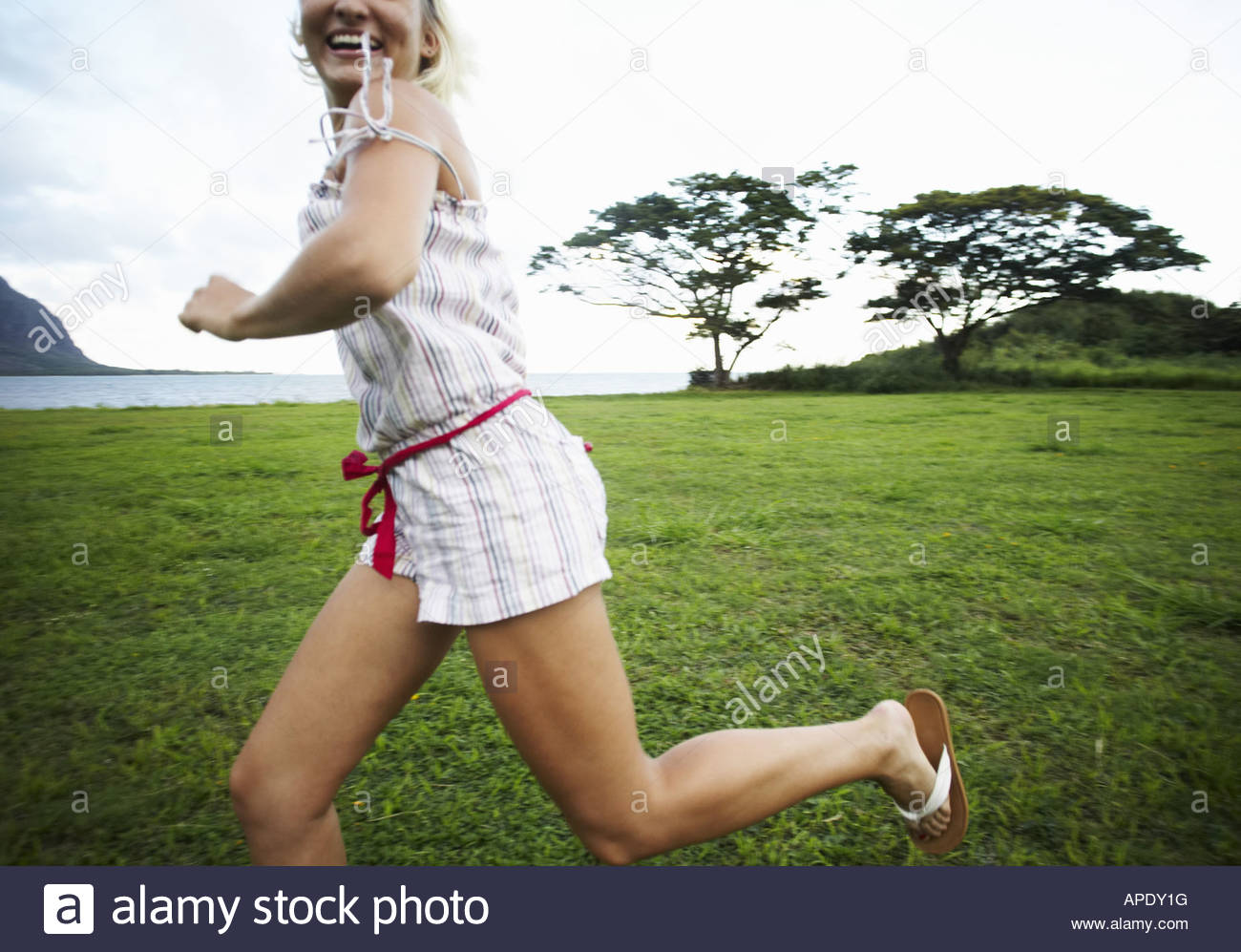 Young woman running through field - Stock Image