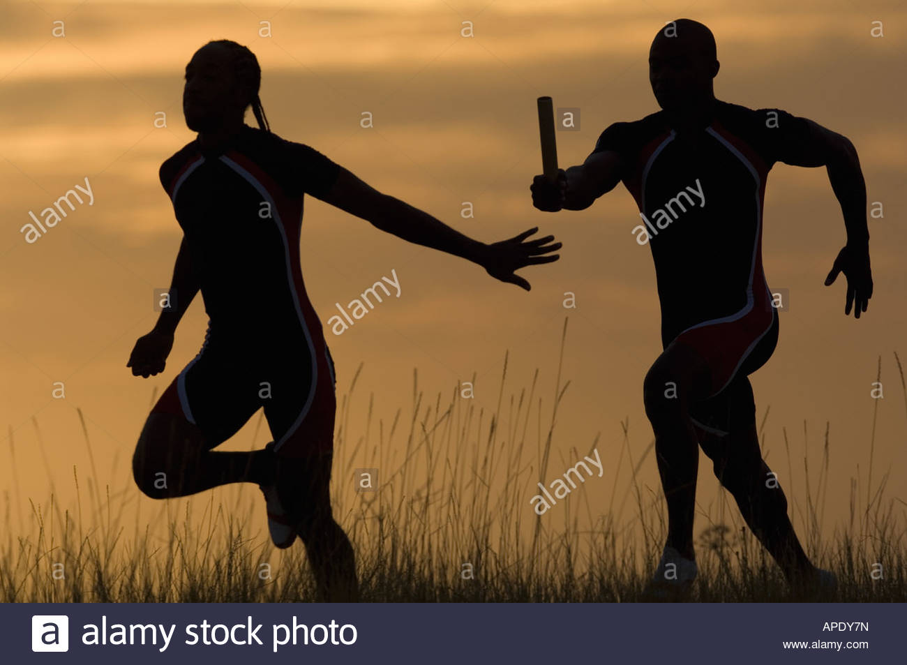 Male athletes running in relay race - Stock Image