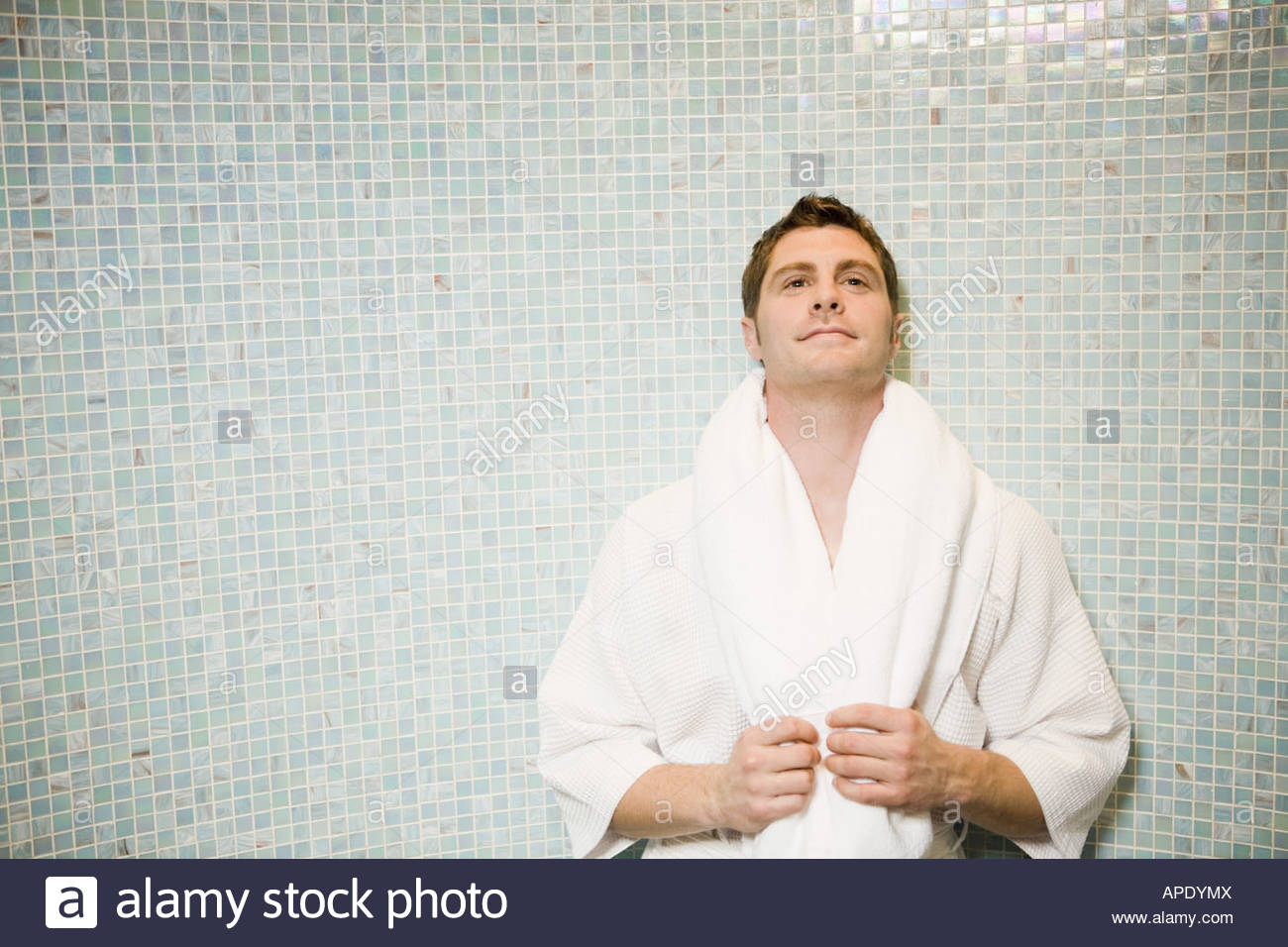 Man in bathrobe leaning on tile wall - Stock Image