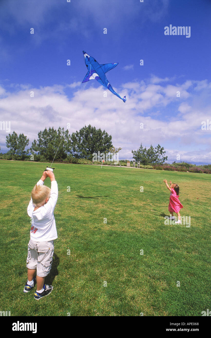 Boy and girl flying kite together - Stock Image