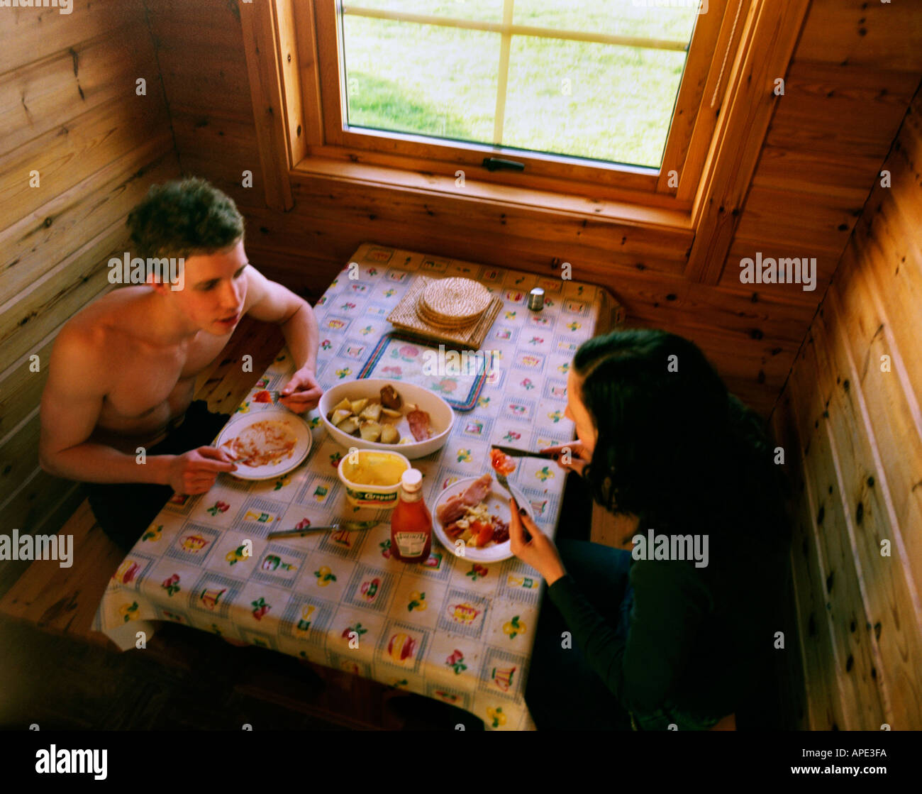 teenage brother and sister eating fried breakfast in a holiday log cabin seen from above - Stock Image