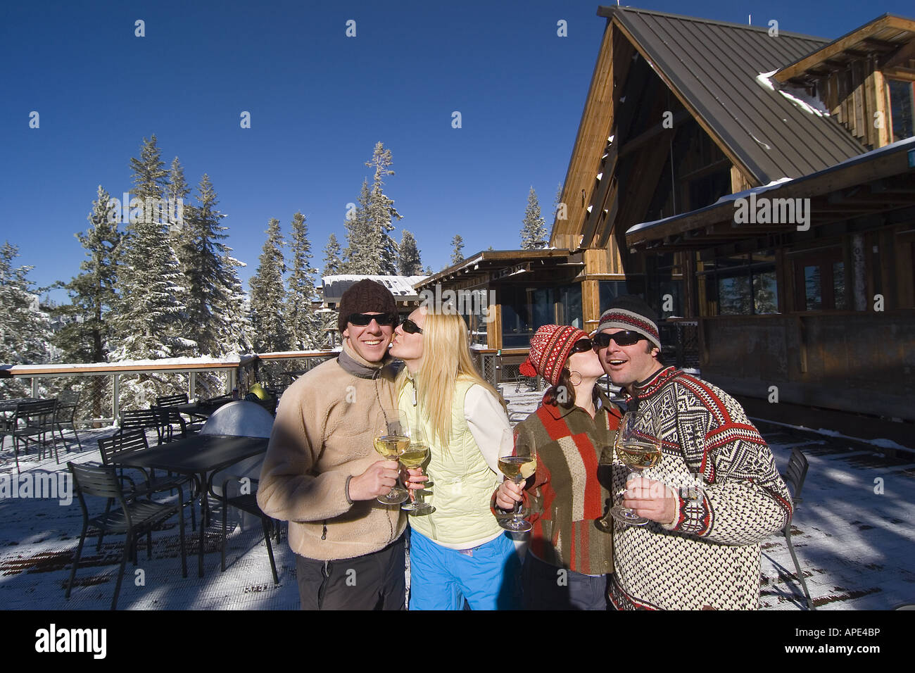 two couples kissing on the deck of a ski lodge on a sunny day in