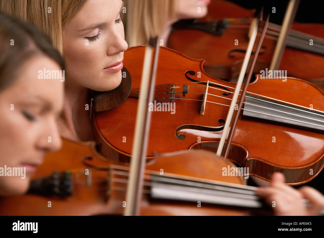 Women Playing Violins in musical group, close-up - Stock Image