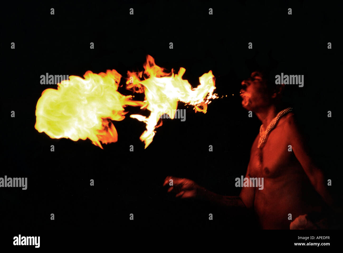 Man performing art of blowing fire out of his mouth - Stock Image