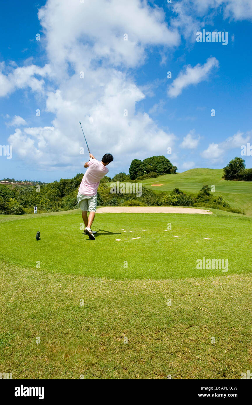 A late twenties male golfer tees off at the Princeville Golf Coarse Princeville Kauai Hawaii USA - Stock Image