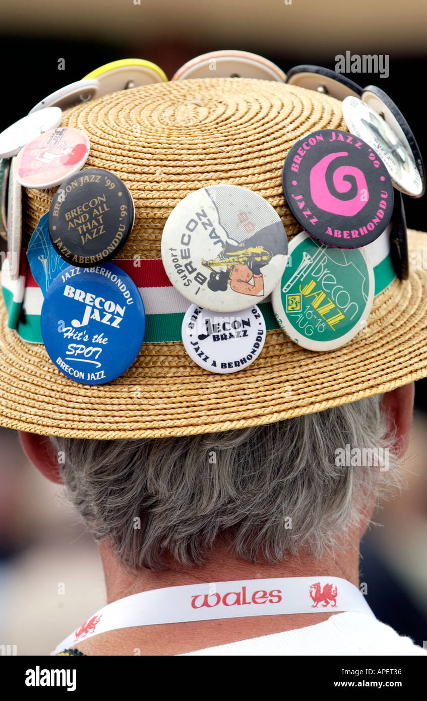 Fan wearing straw boater with badges and red dragon ribbon around his neck at the annual Brecon Jazz Festival Powys Wales UK - Stock Image