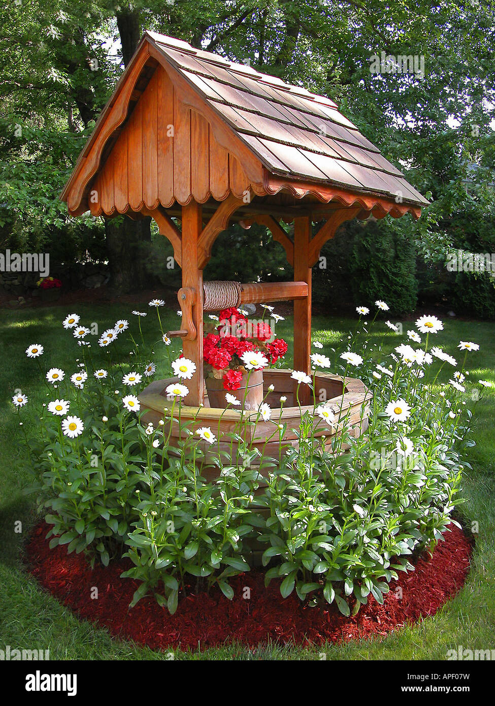 Wishing Well, Made Of Cedar Wood With White Flowers Around In Green,  Manicured Garden
