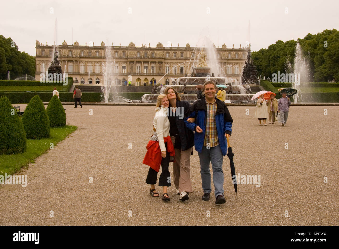 Tourists stand in front of a palace. - Stock Image