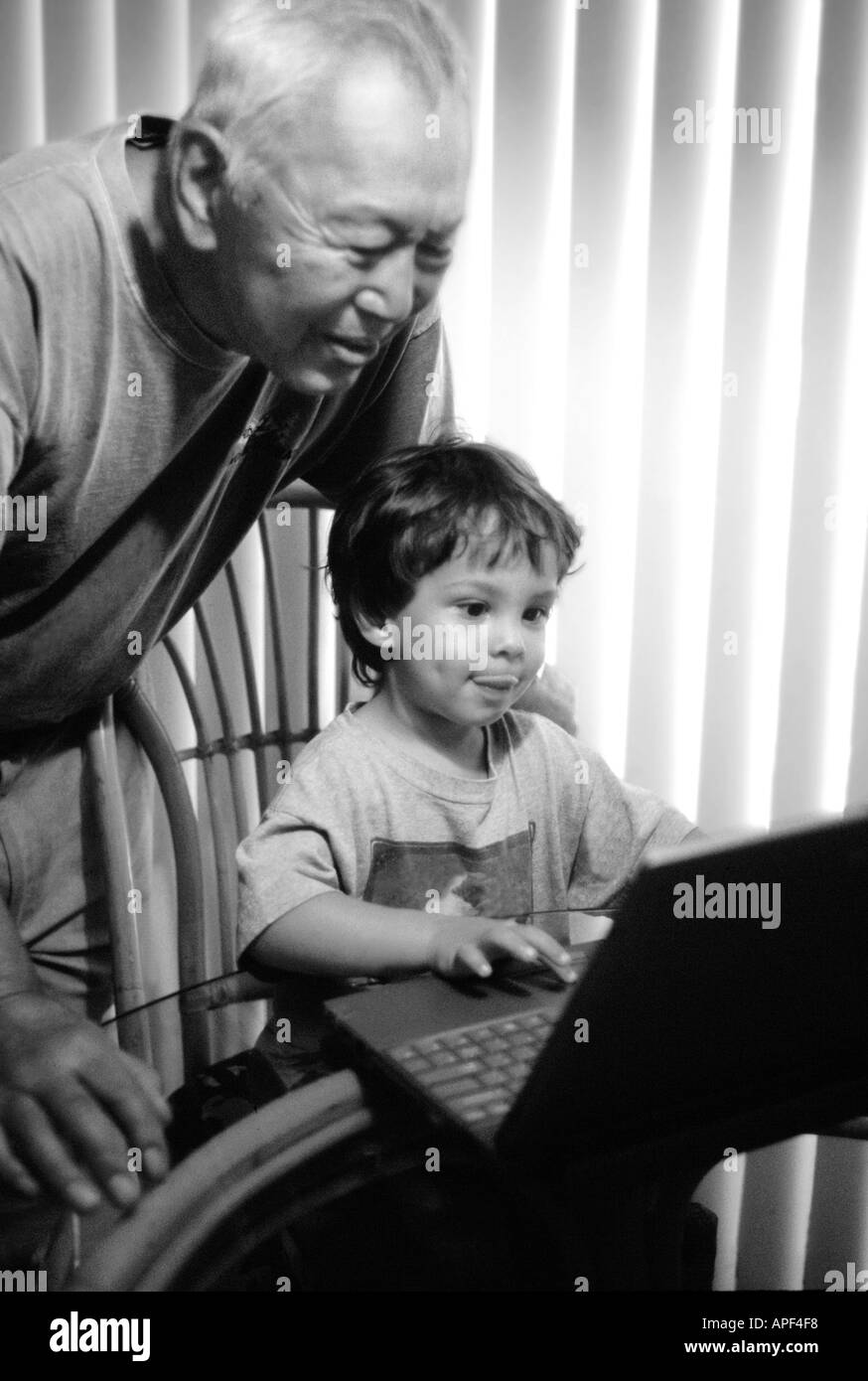4 year old boy showing elderly asian man how to use lap top computer. B&W. Vertical - Stock Image