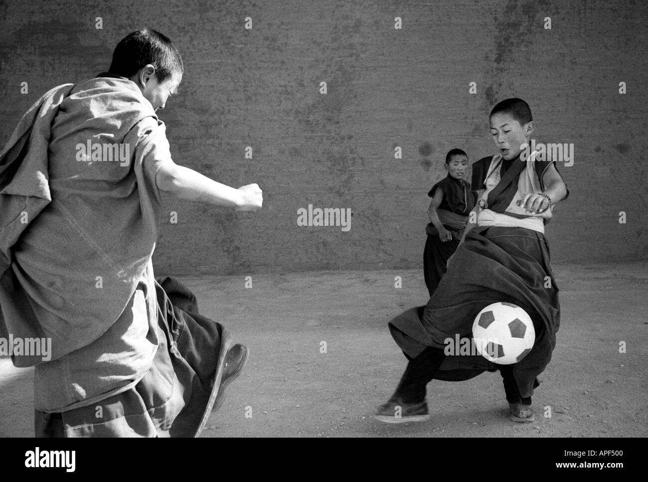 Yellow Hat Monks playing football in the Xiahe monastery Gansu Province Peoples Republic of China Stock Photo