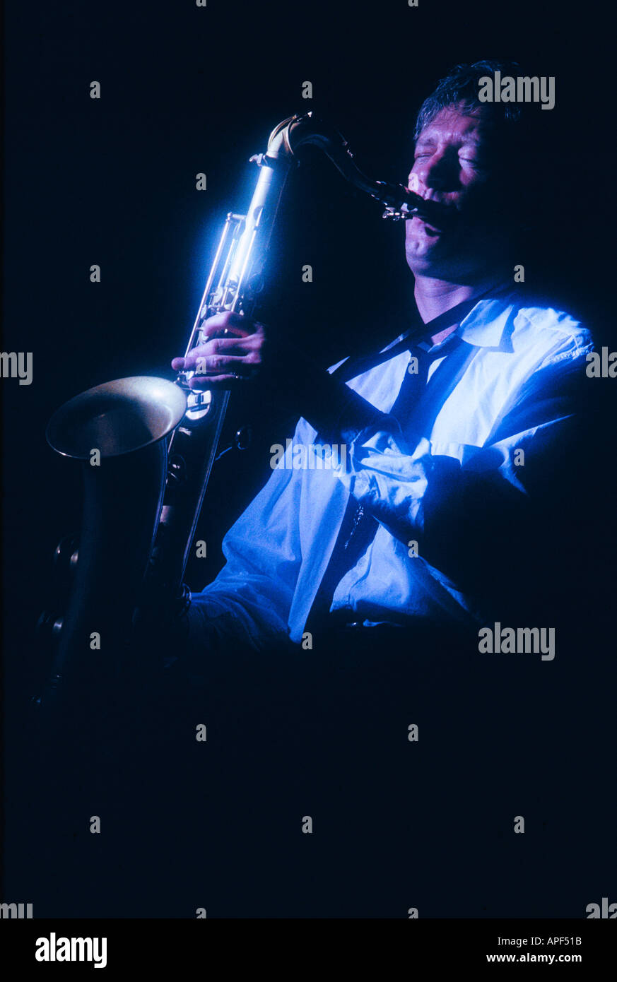 Young man playing tenor saxophone.  Blue light Night club atmosphere - Stock Image