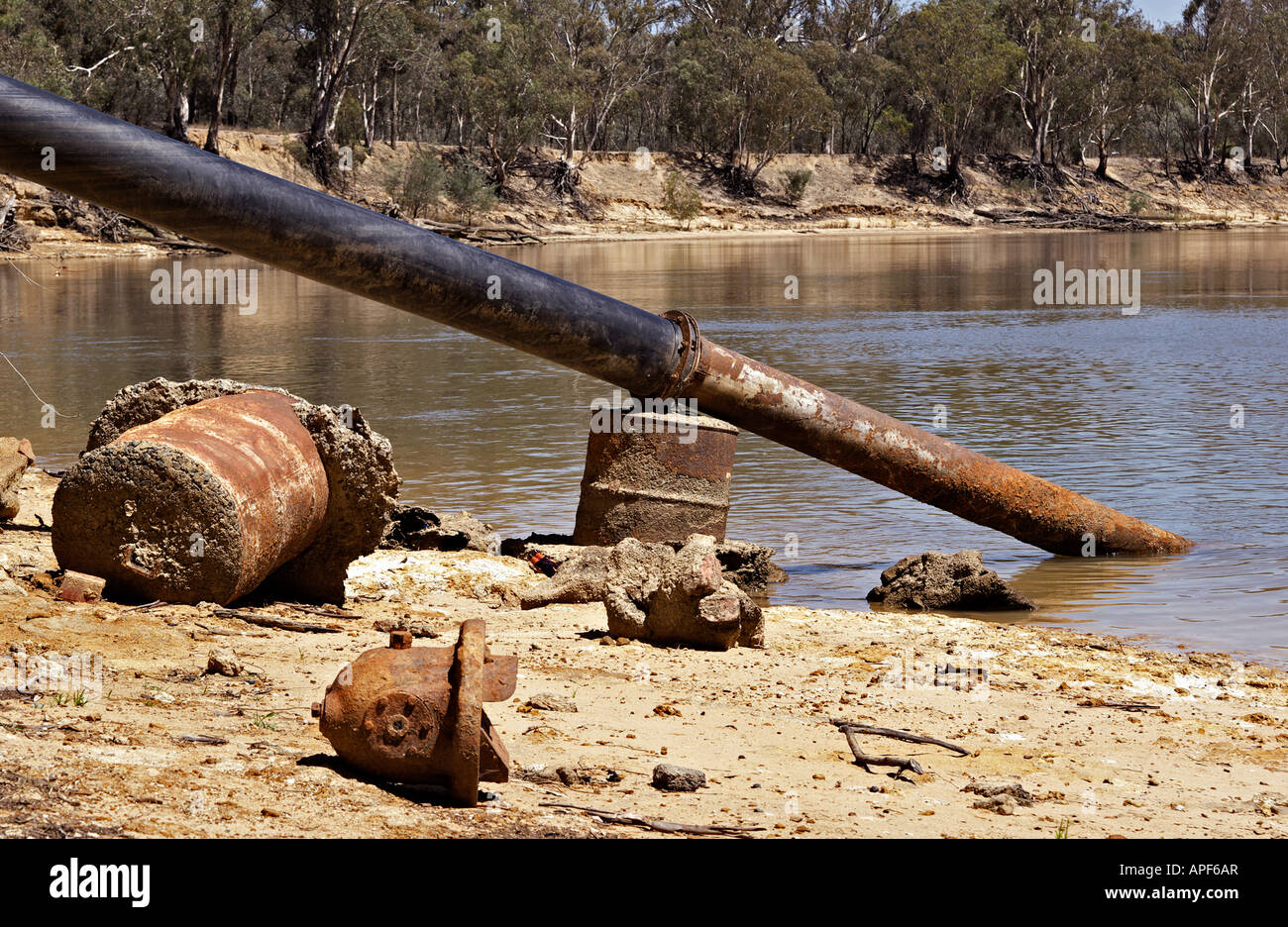 old rusty metal and pipe going into the river Stock Photo