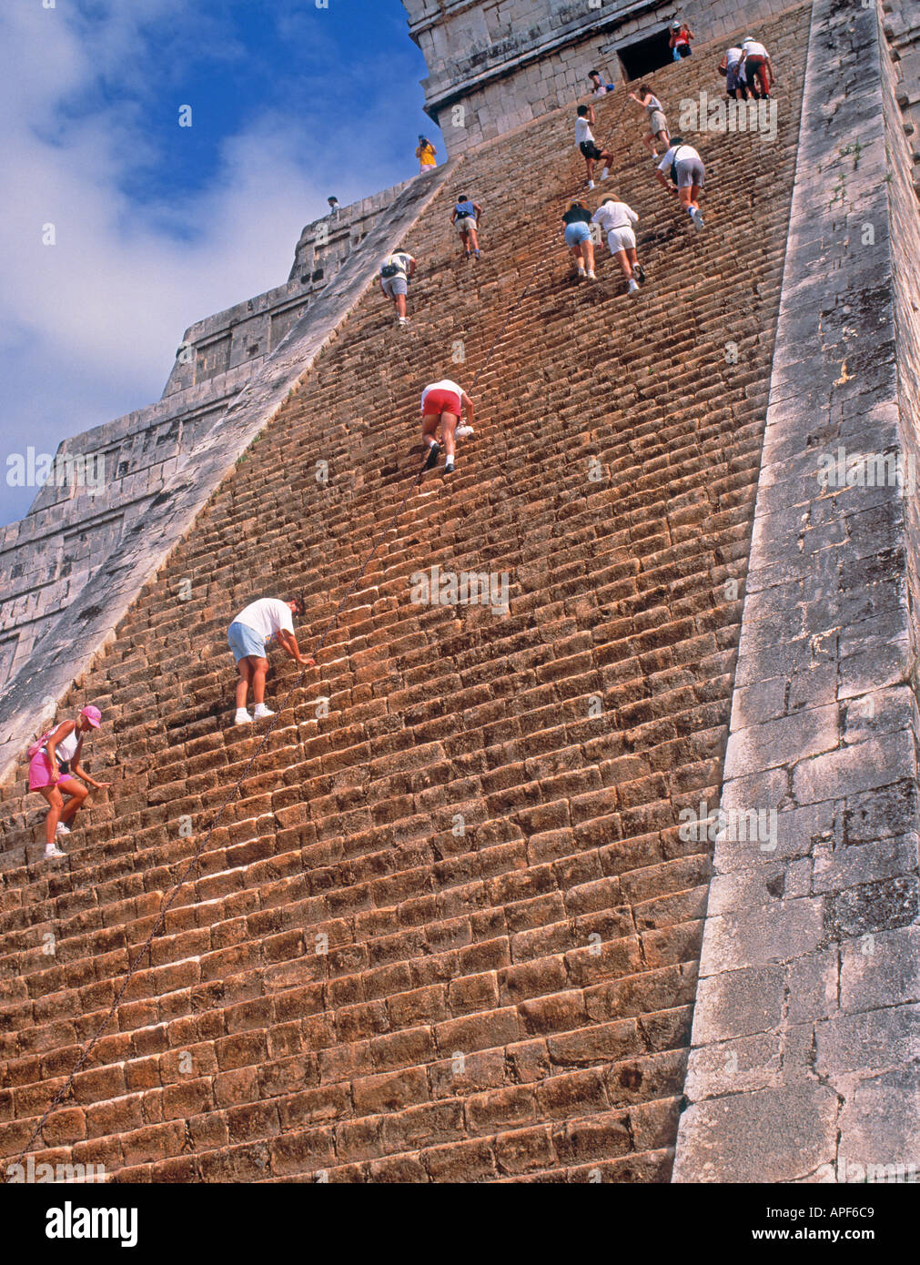Chichen Itza, Yucatan State, Mexico.  Tourists climbing steep steps of The Castle or Kukalcan's Pyramid - Stock Image