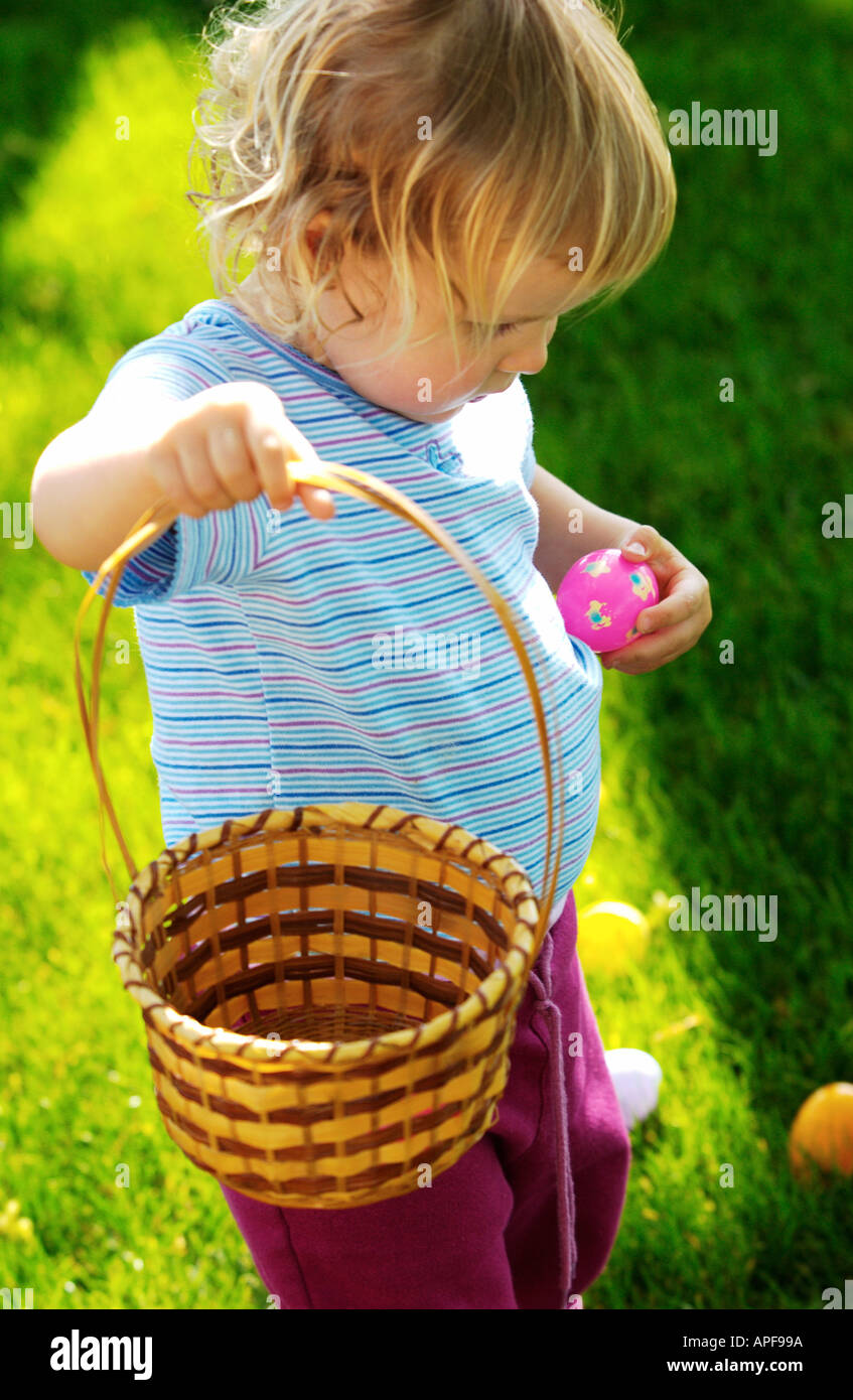 Two year old girl holding easter basket and pink easter egg - Stock Image
