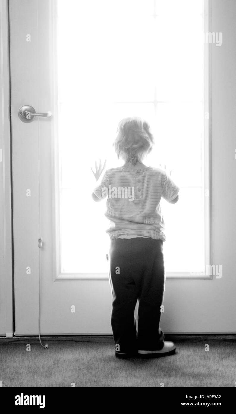 Young girl looking out window Stock Photo