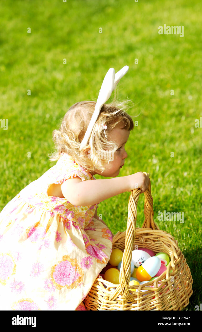 Two year old girl holding easter basket wearing bunny ears - Stock Image