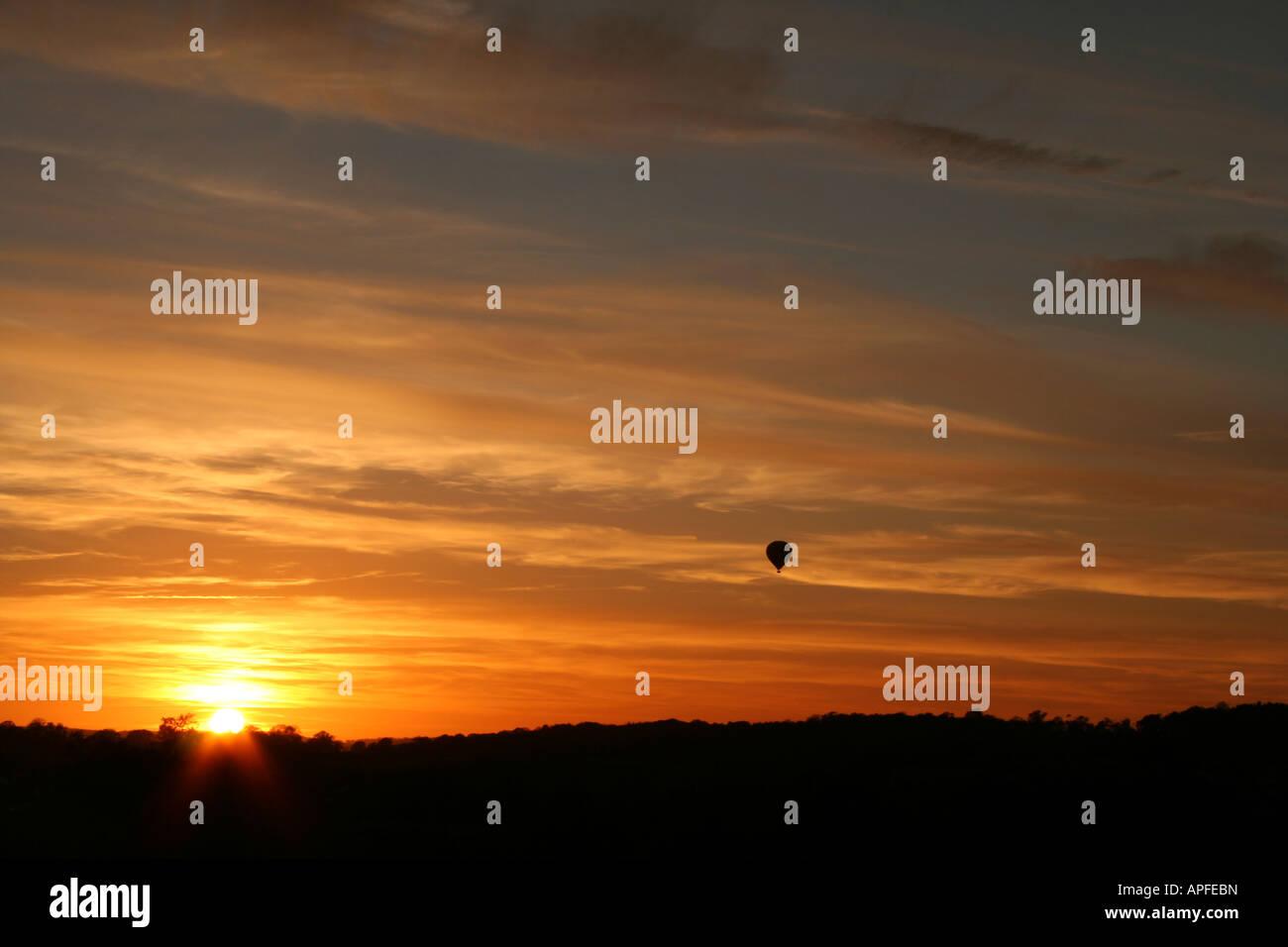 Baloon into sunset - Stock Image