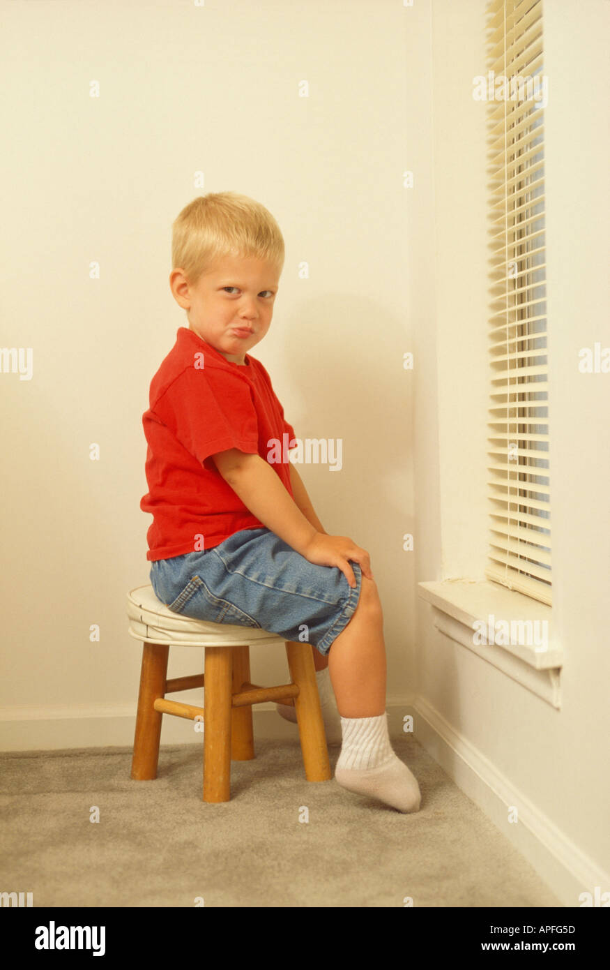 Three Year Old Sitting On Stool For Time Out Stock Photo