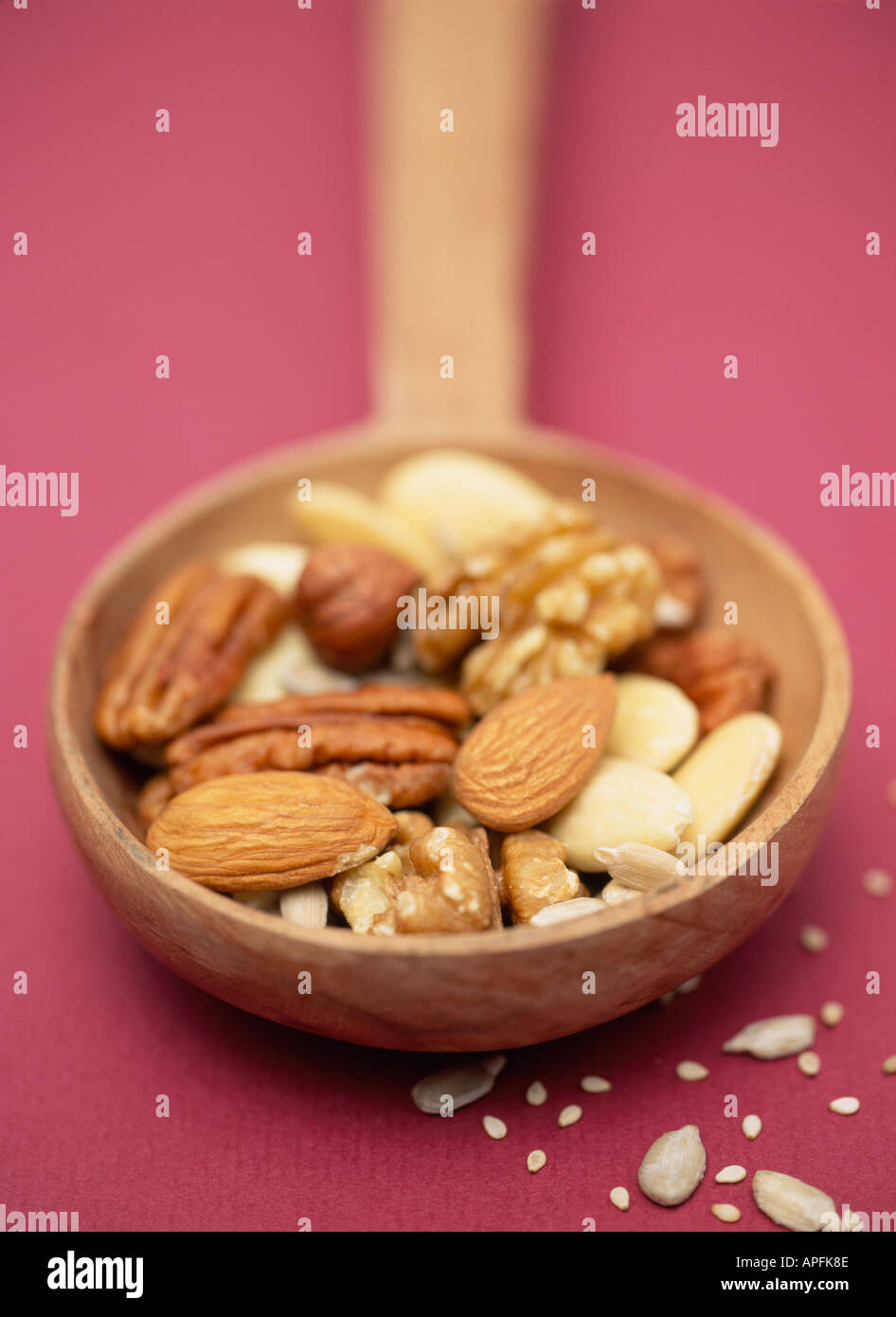 Selection of nuts and seeds on a wooden spoon on dark purple background - Stock Image