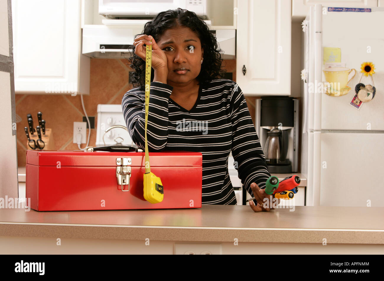 Woman looking hopeless with toolbox and tools - Stock Image