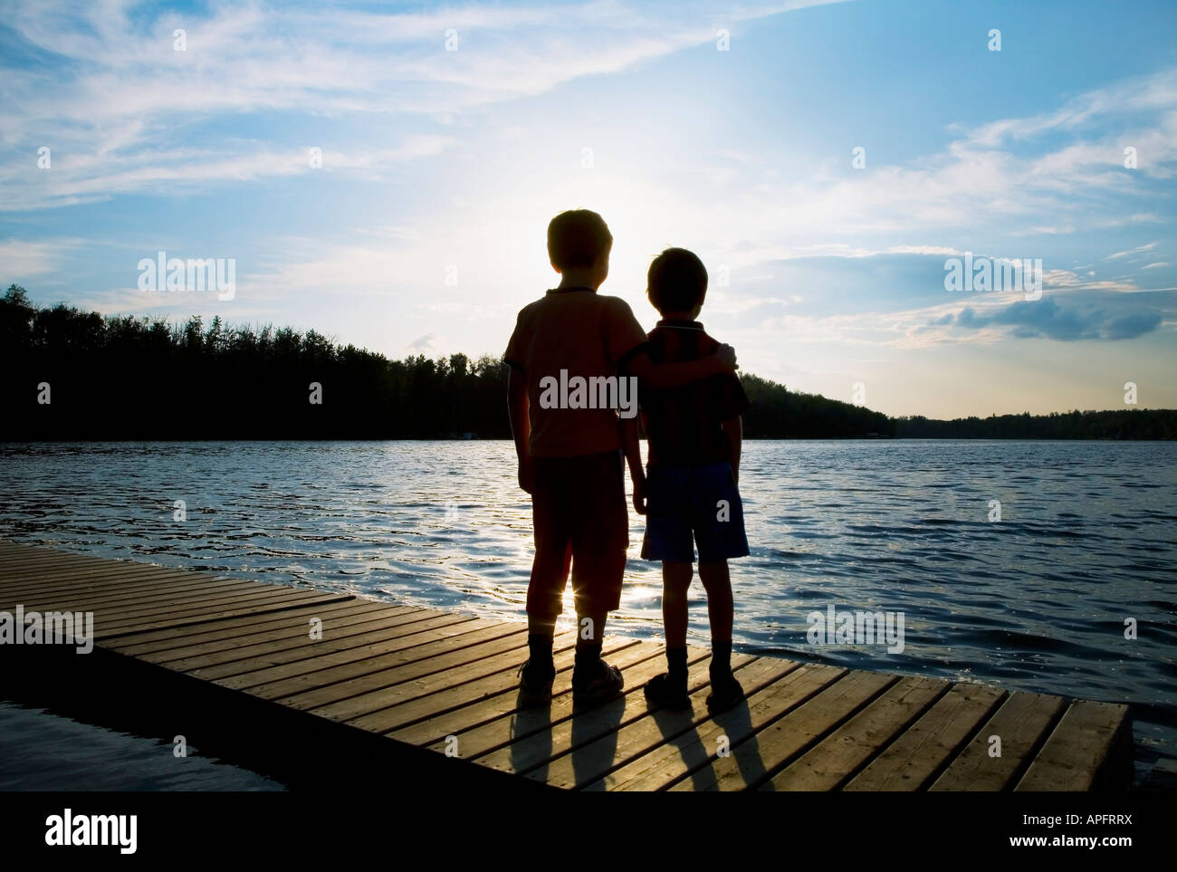 Silhouette of children on a dock - Stock Image