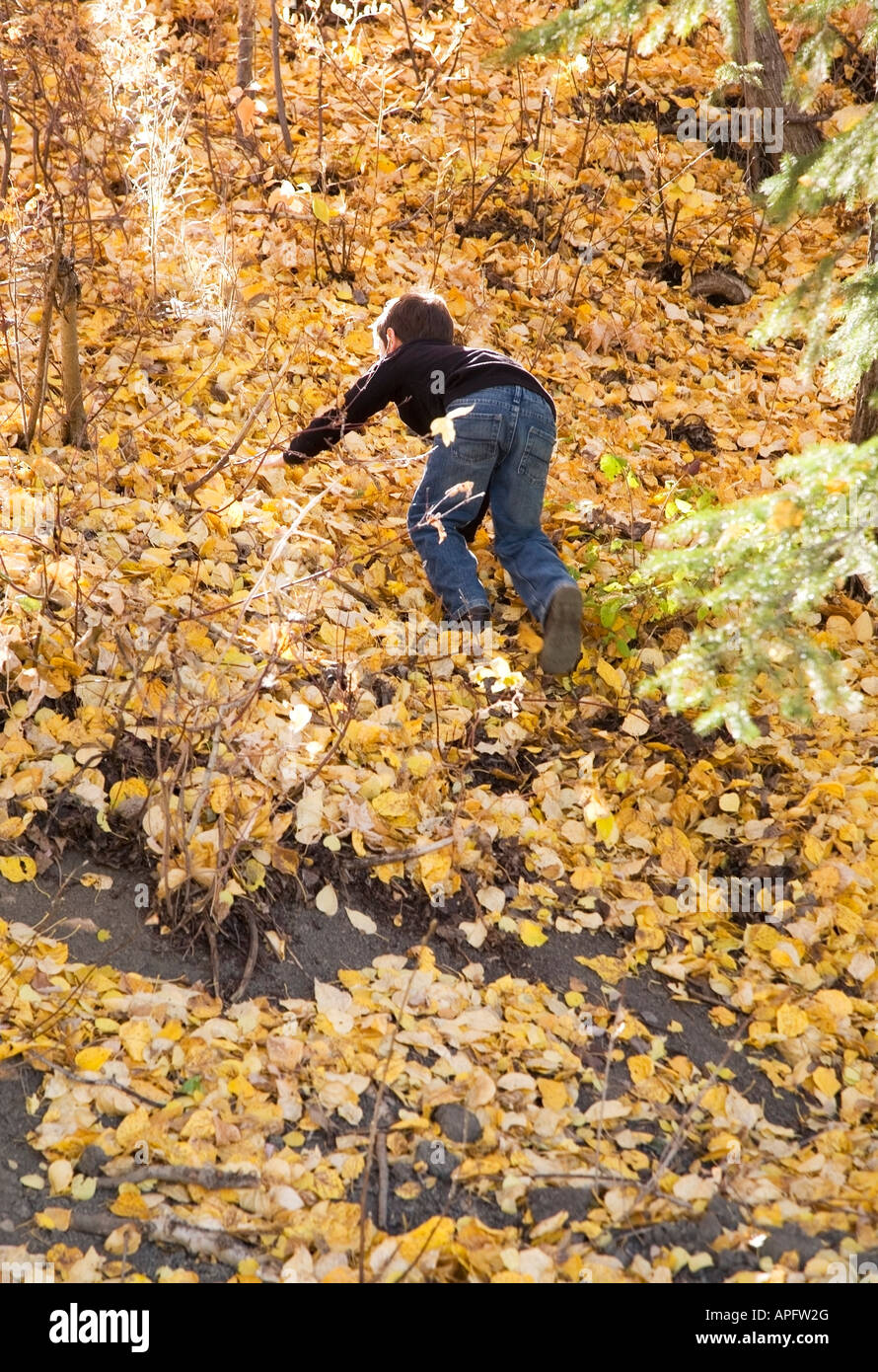 Boy climbing a steep hill in fall - Stock Image