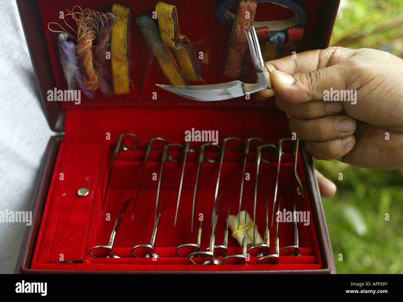 A Filipino selects a blade for his fighting bird at a cockhouse in Oriental Mindoro, Philippines. Stock Photo