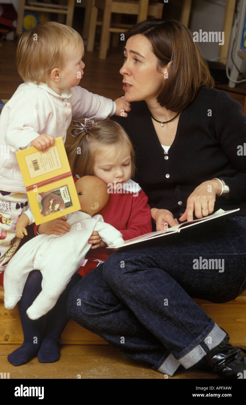 mother reading to two children - Stock Image