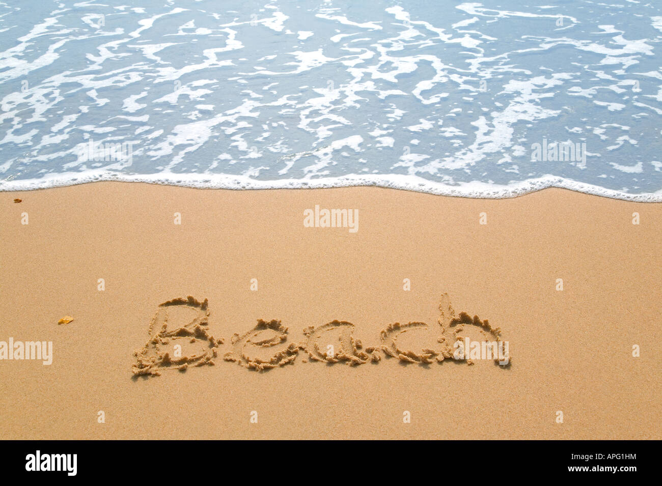 Beach written on a golden sandy beach next to the waters edge Stock Photo
