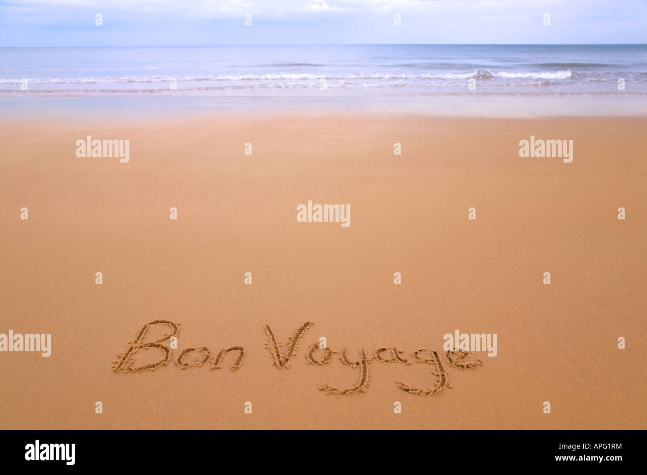 Bon Voyage written in sand on a golden sandy beach sea and horizon in the distance - Stock Image