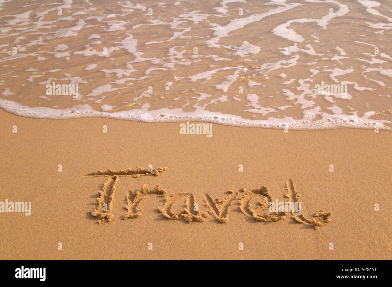 Travel written in sand on the shoreline of a golden sandy beach - Stock Image