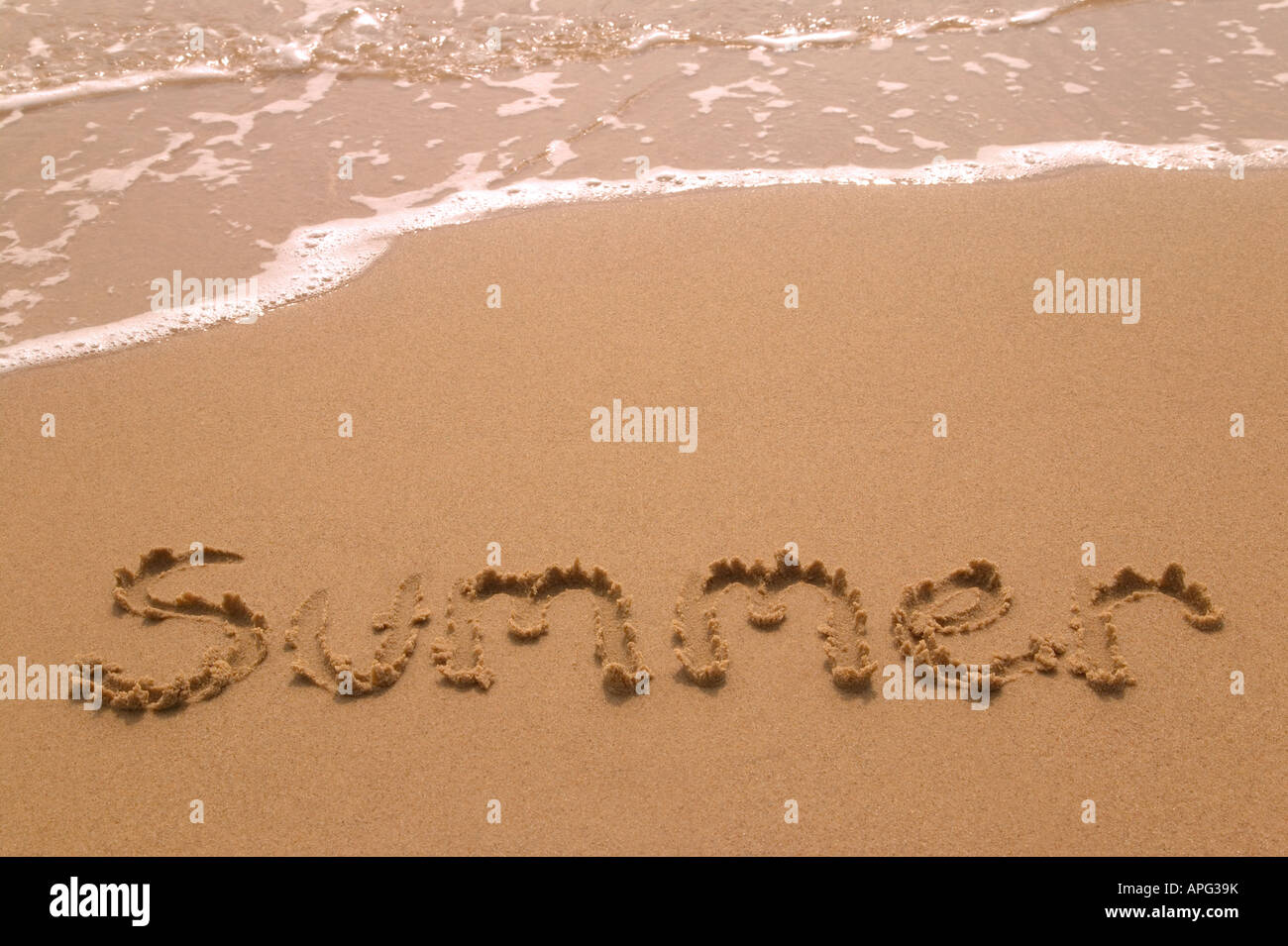 Summer written in golden sand on the shoreline as the waves come in - Stock Image
