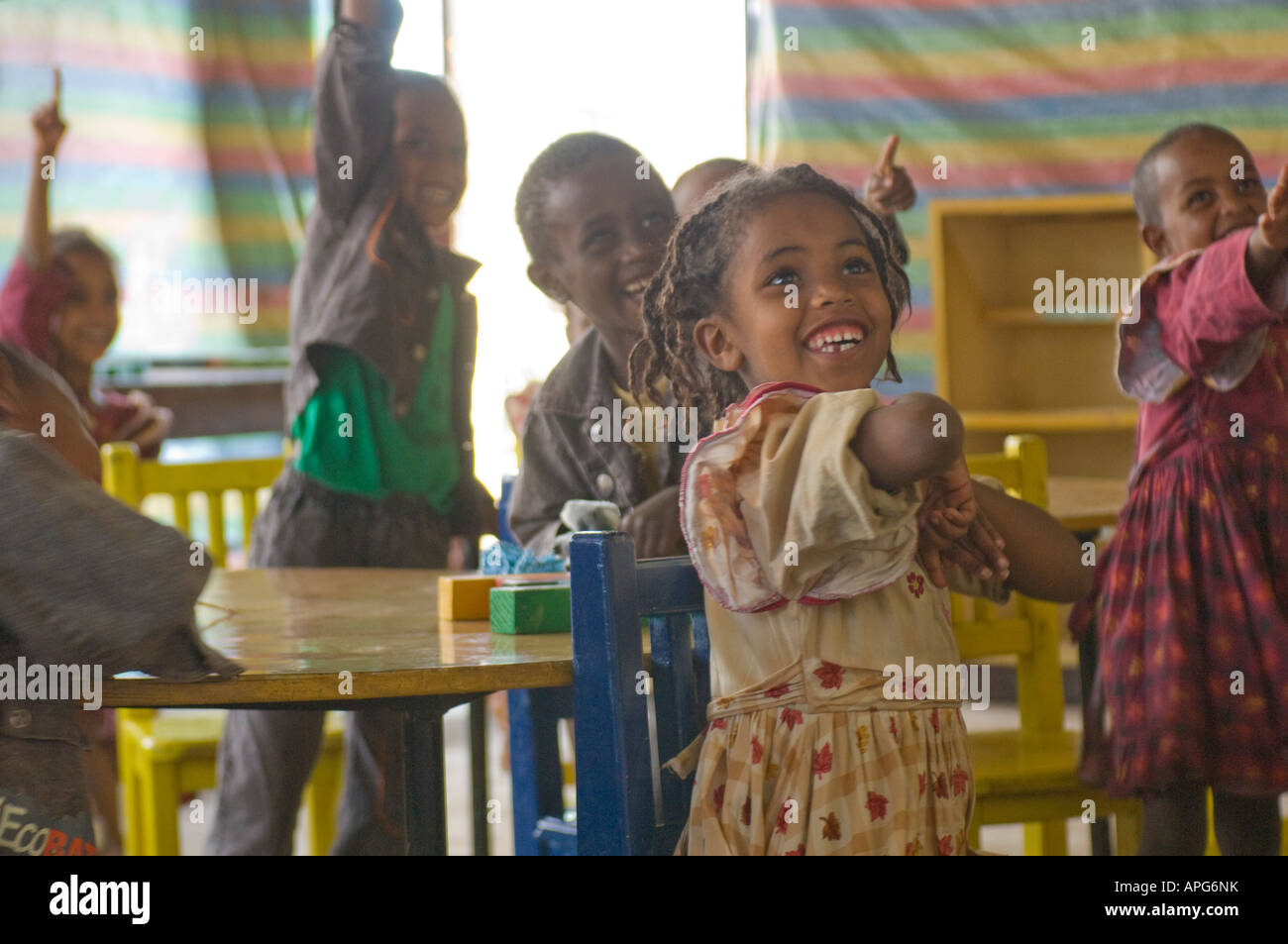 Children smile and put up their hand eagerly to answer a question in the classroom of a charity run school. - Stock Image