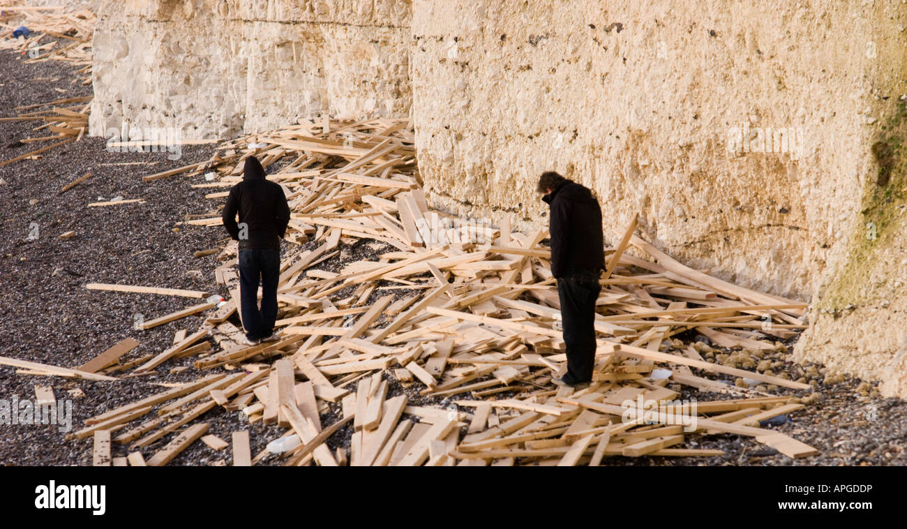 Two men walk amongst the sawn timber cargo washed up on Sussex beaches following the sinking of the Ice Prince. - Stock Image