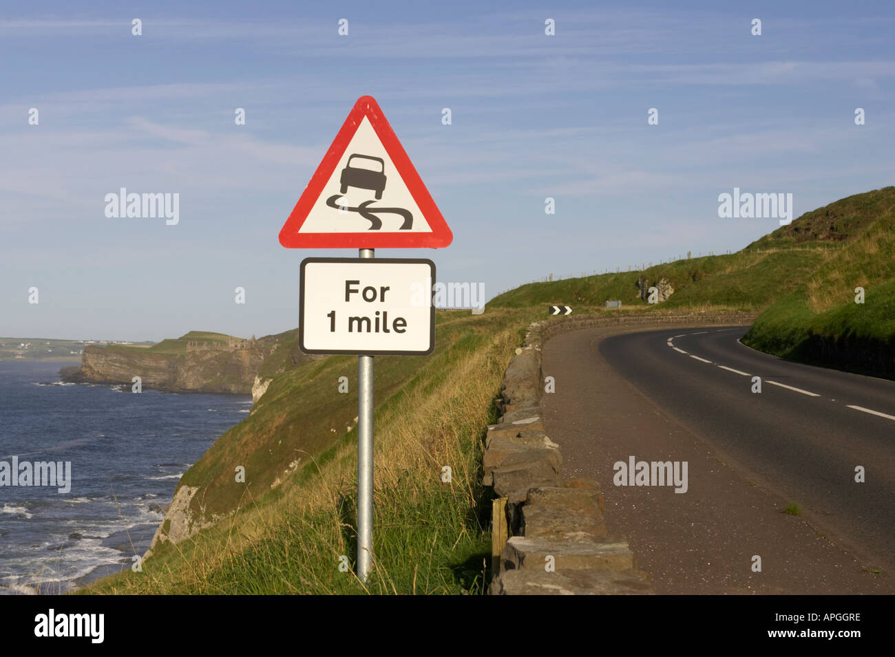 triangular red lined slippery road for one mile warning road sign on the A2 coast road near bend with Dunluce Castle in the back - Stock Image