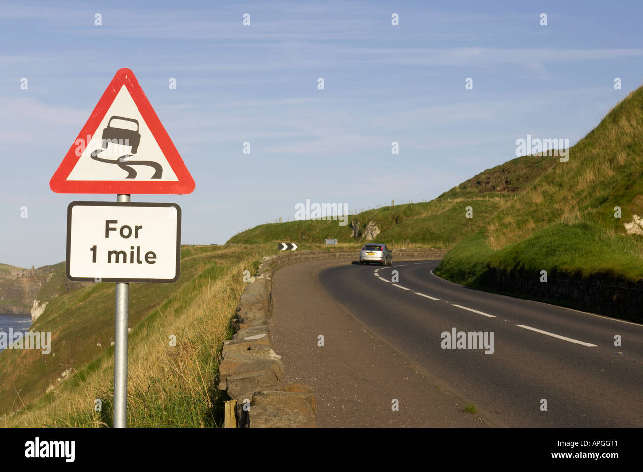 triangular red lined slippery road for one mile warning road sign on the A2 coast road with car at bend near Dunluce Castle - Stock Image