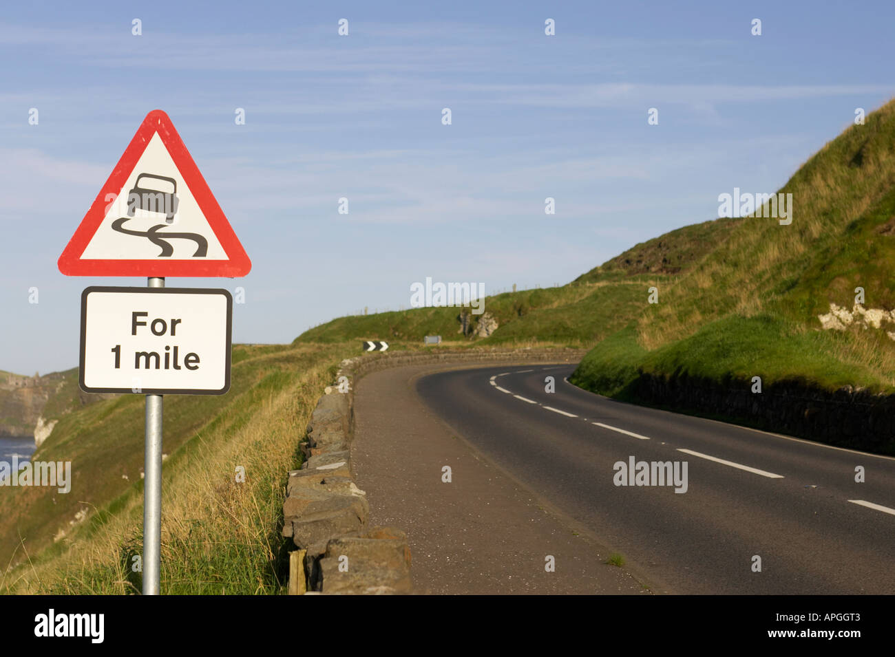 triangular red lined slippery road for one mile warning road sign on the A2 coast road at bend near Dunluce Castle - Stock Image