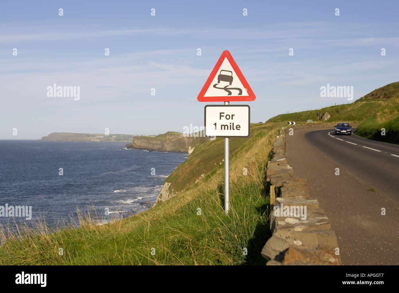 triangular red lined slippery road for one mile warning road sign on cliff on the A2 coast road with Dunluce Castle and sea - Stock Image