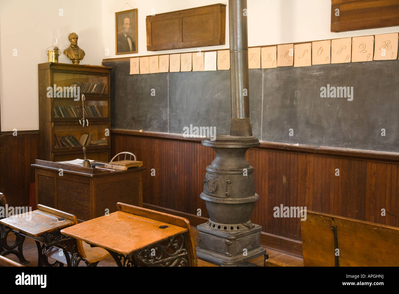 ILLINOIS Rockford Wooden desks with inkwell for students old fashioned schoolhouse pot bellied stove teachers desk - Stock Image
