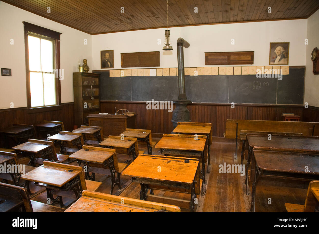 ILLINOIS Rockford Wooden desks with inkwell for students old fashioned schoolhouse pot bellied stove Midway Village - Stock Image