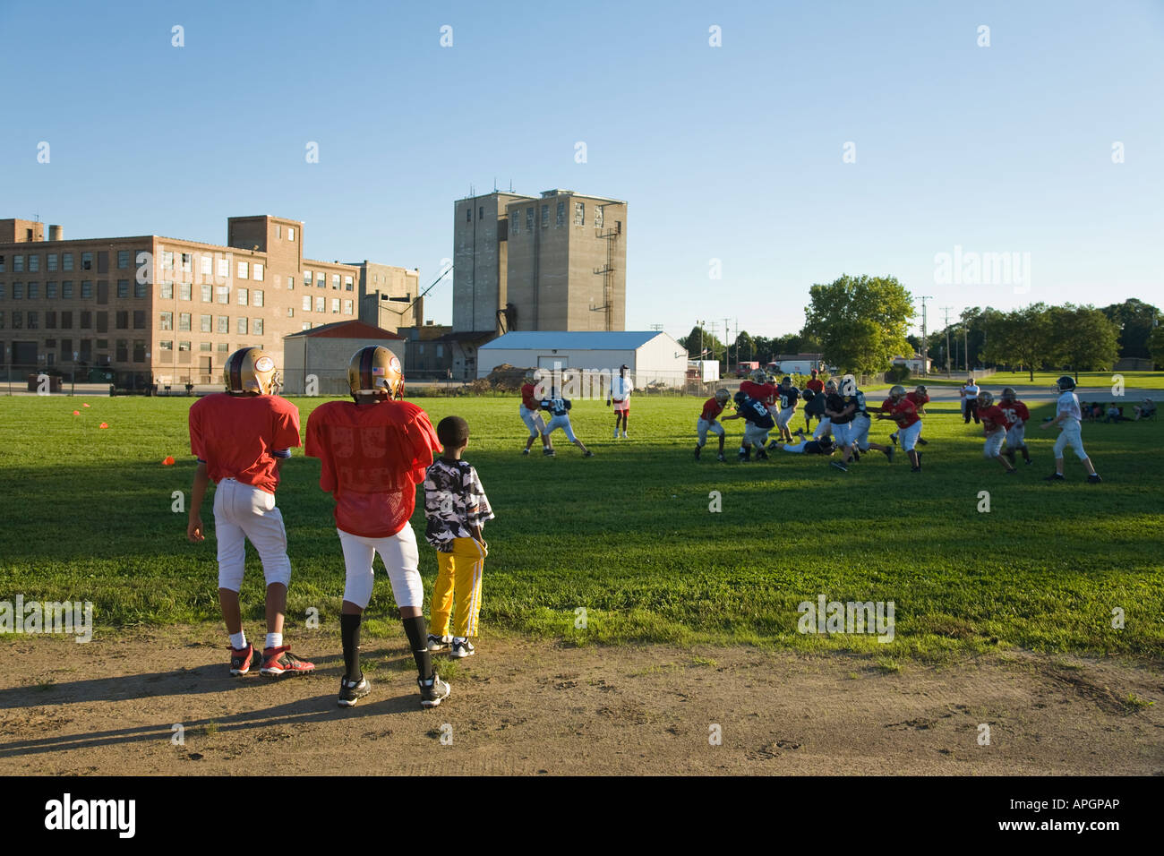 WISCONSIN Racine Two boys in football uniforms watching game in field junior high students playing - Stock Image