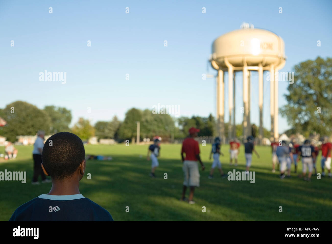WISCONSIN Racine African American boy watching football game in field junior high students playing water tower in - Stock Image