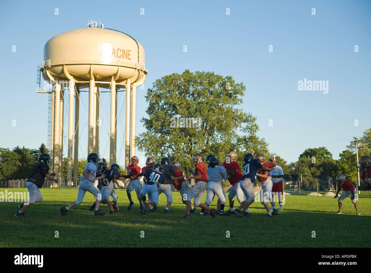 WISCONSIN Racine Junior high boys playing football game in field water tower town name painted on side - Stock Image