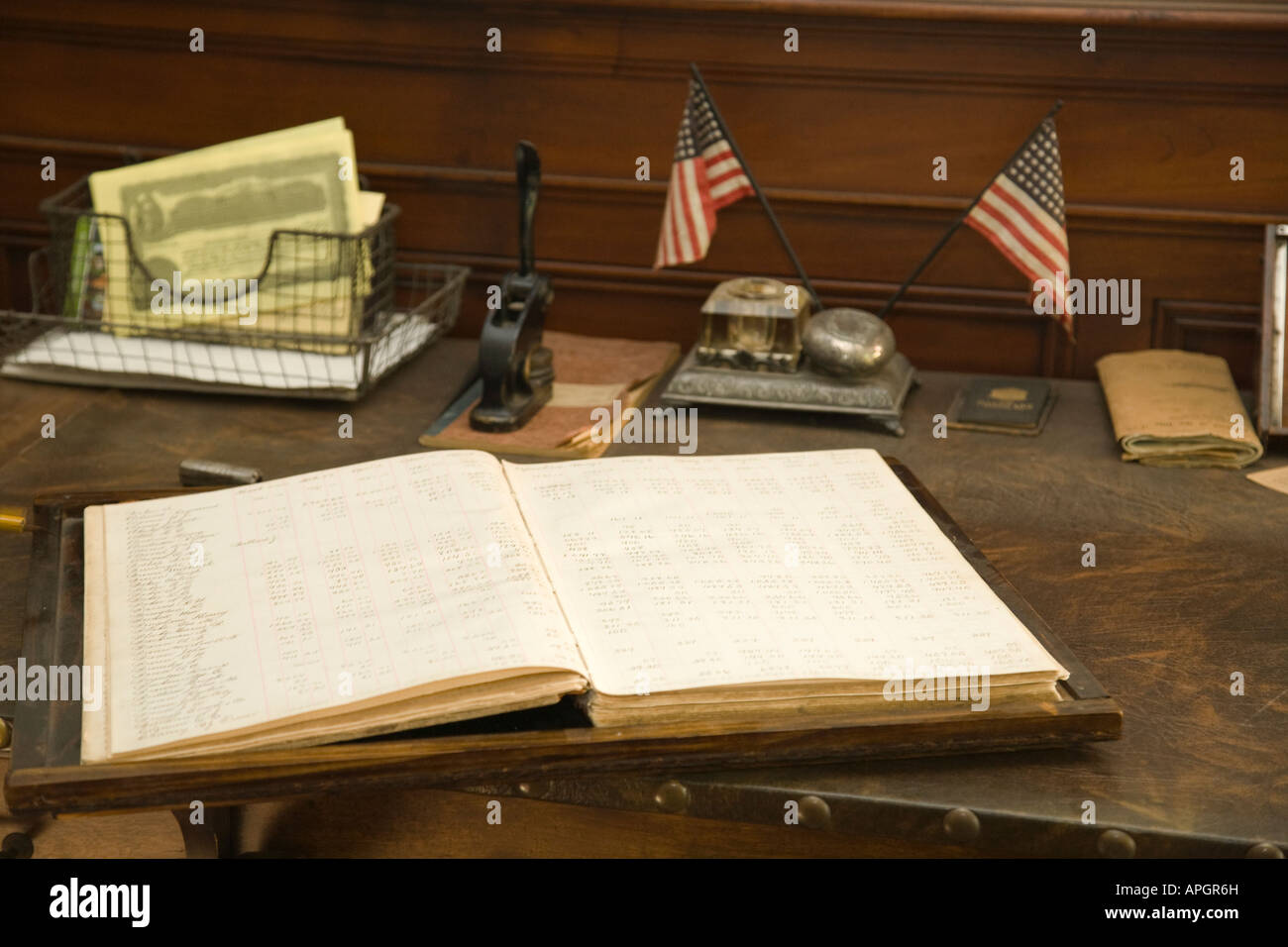 ILLINOIS Rockford Wooden desk with ledger rubber stamps and flags old fashioned office in historic Midway Village - Stock Image