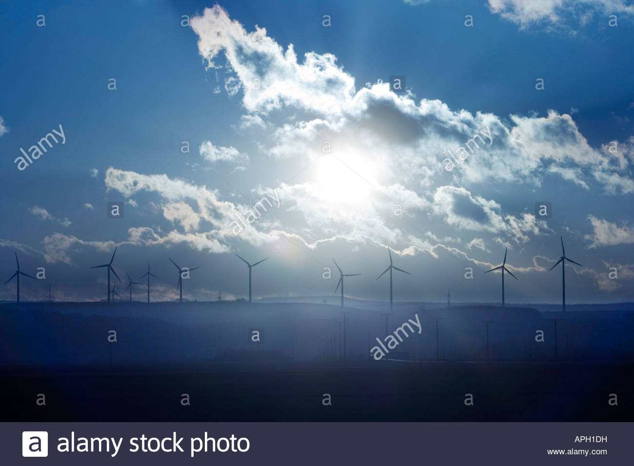 Sunset behind wind wheels - Stock Image
