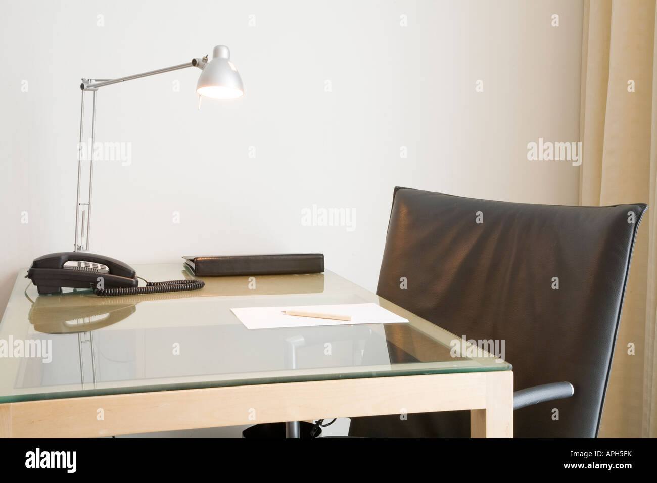 desk with lamp and black leather swivel chair could depict an