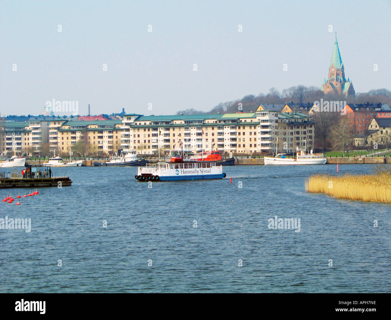 A ferry crosses the Hammarby Sjö lake in the modern residential area Hammarby Sjöstad in Stockholm, Sweden. - Stock Image