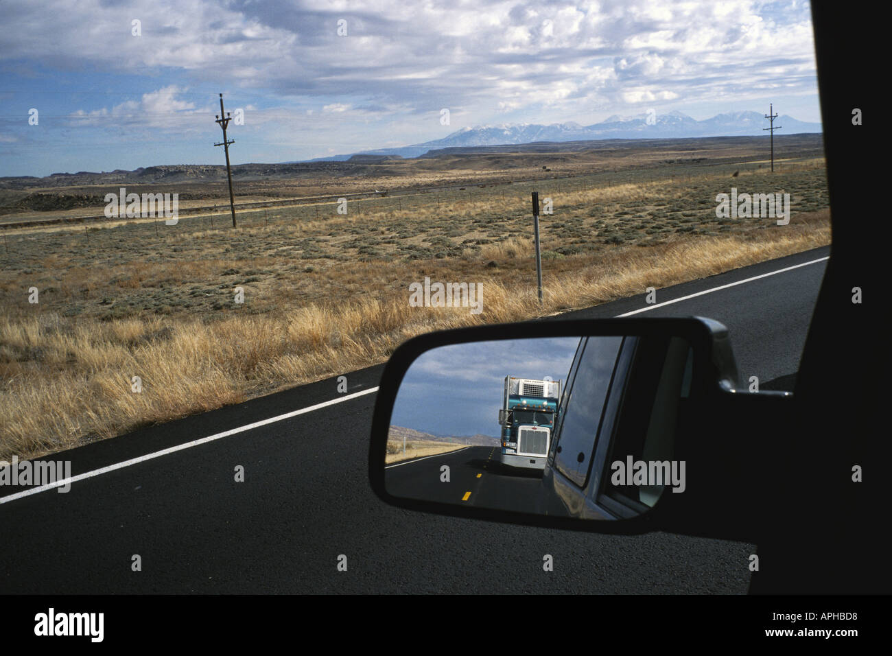 View behind from drivers seat of truck in rear view mirror on highway near Moab Utah with the LaSal Mountains in - Stock Image