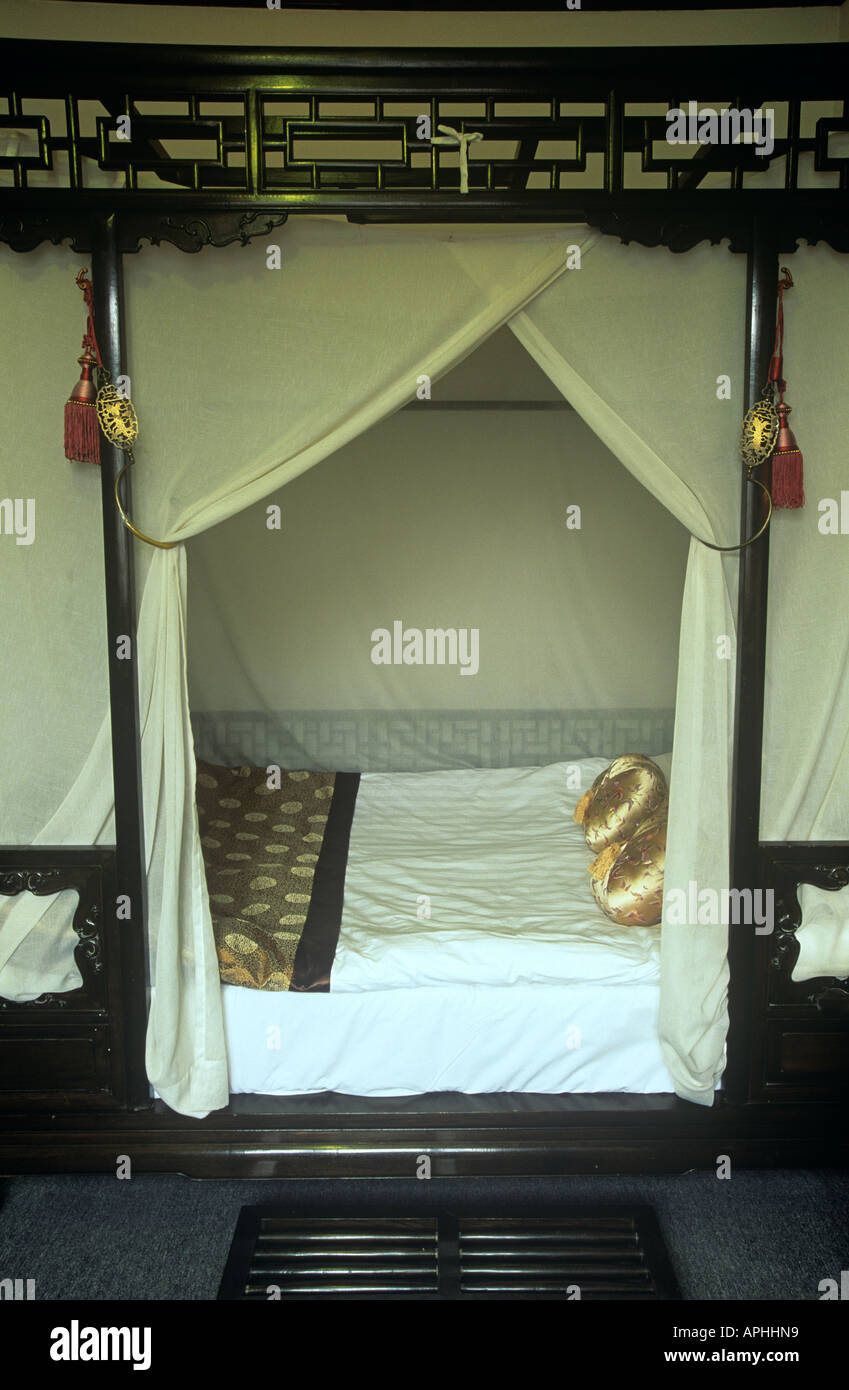 Very grand four poster bed in a bedroom of the Lusong Yuan Hotel on Banchang Hutong Street in Beijing - Stock Image